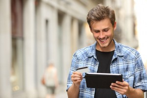man purchasing something on his tablet, holding his credit card